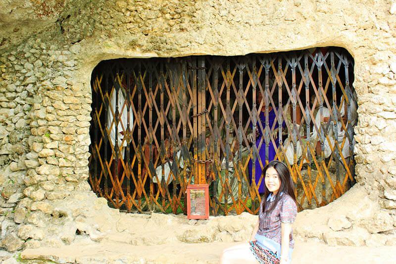girl smiling sit in front of tau tau wooden dolls trapped inside cave toraja kete kesu_agirlnamedclara