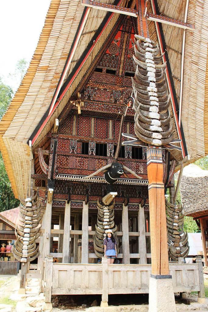 girl solo trip standing at kete kesu tongkonan entrance buffalo horns stack toraja indonesia_agirlnamedclara