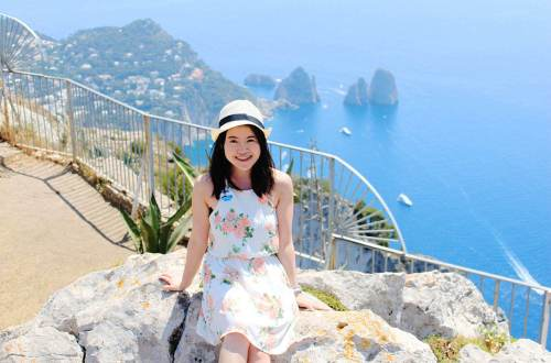 sunny day asian girl black hair smile sit on rock blue sea background top of capri italy_agirlnamedclara