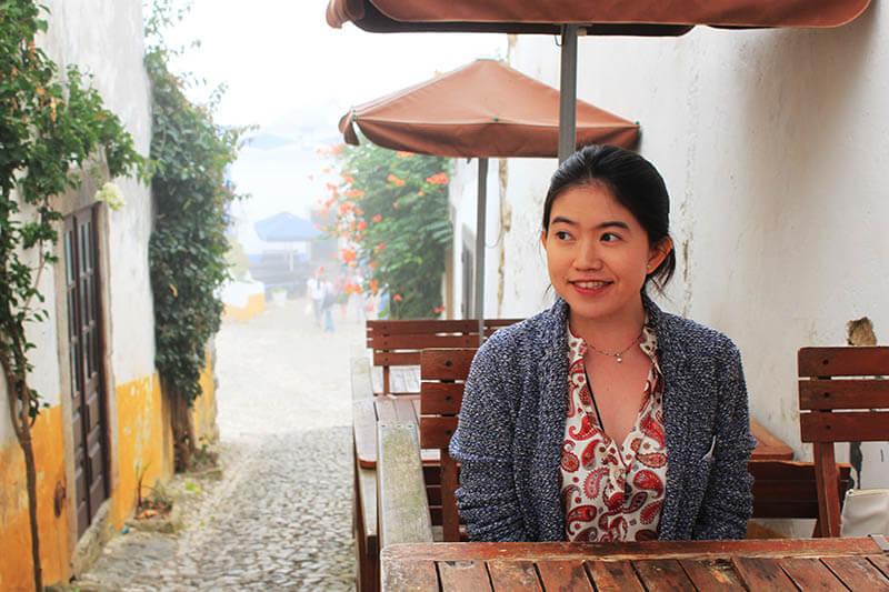 asian girl sit smiling background cobbled street flower mist obidos agirlnamedclara