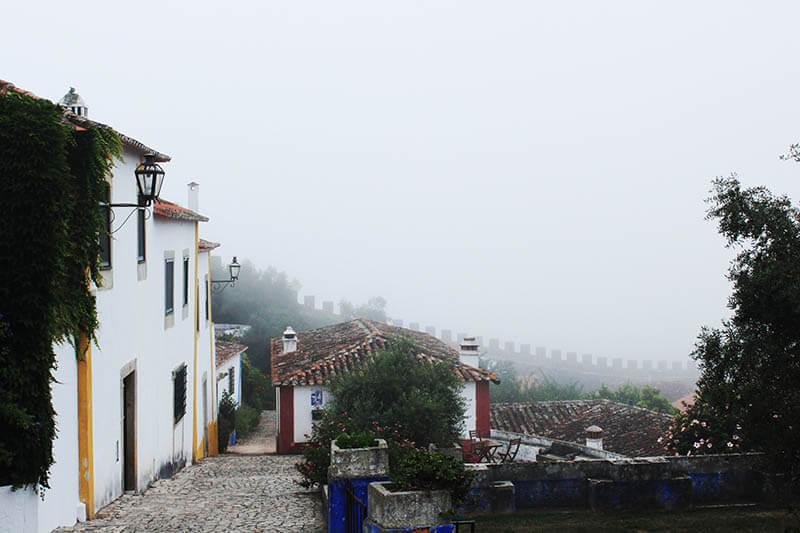 cobbled street house misty morning obidos portugal agirlnamedclara