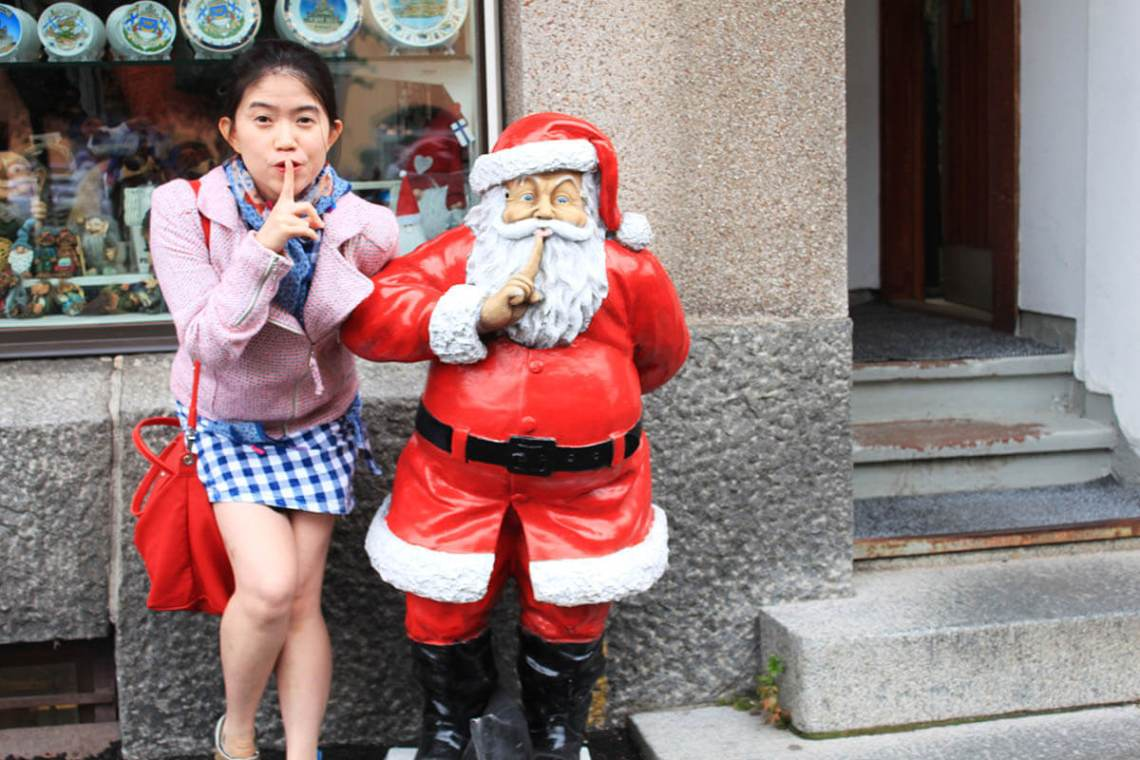asian girl tourist pink jacket hush pose with santa claus helsinki finland travel agirlnamedclara