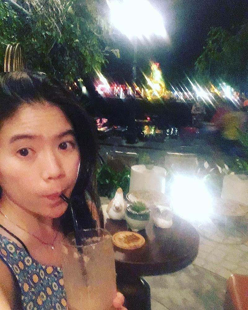 girl sipping drink bird cafe hoi an night agirlnamedclara