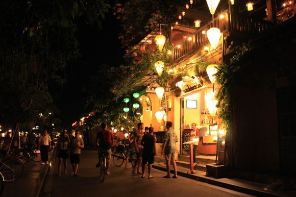 tourist stand outside a cafe hoi an night market agirlnamedclara