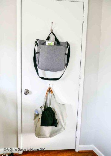 hooks on back of door holding diaper bags