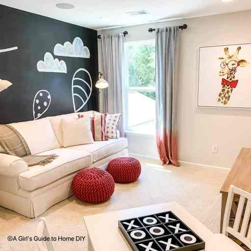 room with couch and chalkboard wall