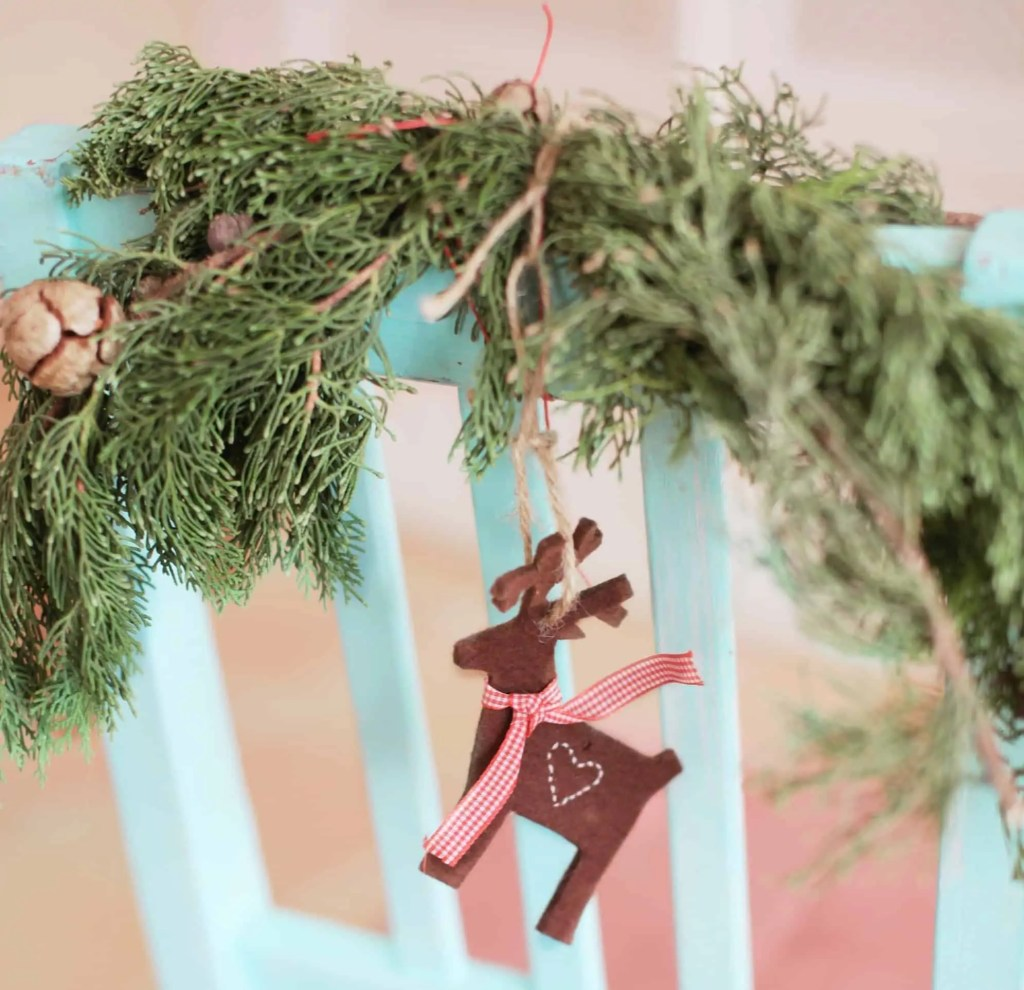 A homemade Christmas decoration hanging on an evergreen branch