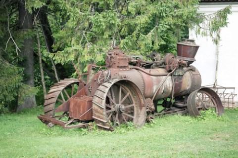 Old rusty farming tractor near barn