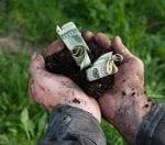 Man holding soil with dollars spending