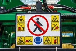 Panel with safety warning signs at work, placed on agricultural equipment.