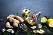 Ginger tea with lemon, lime and mint. Beside the ingredients for tea, the same as the mint leaves, chopped ginger root, slices of lemon and lime. The concept of treatment of colds folk methods.