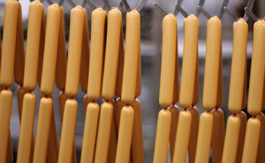 Hot dogs hanging in factory