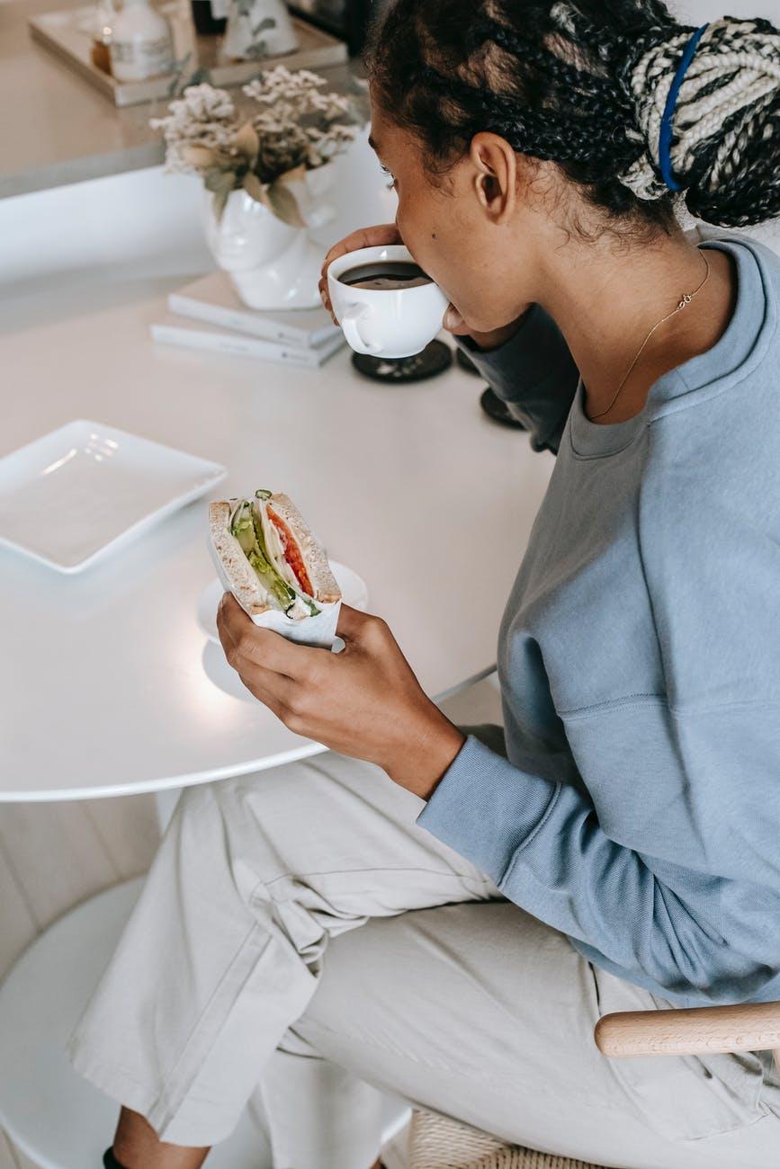 black woman having breakfast in kitchen