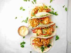 Four bang bang shrimp tacos with bang bang sauce drizzled on top on a white background. Cilantro is scattered and there is a metal ramekin of bang bang sauce on the side.