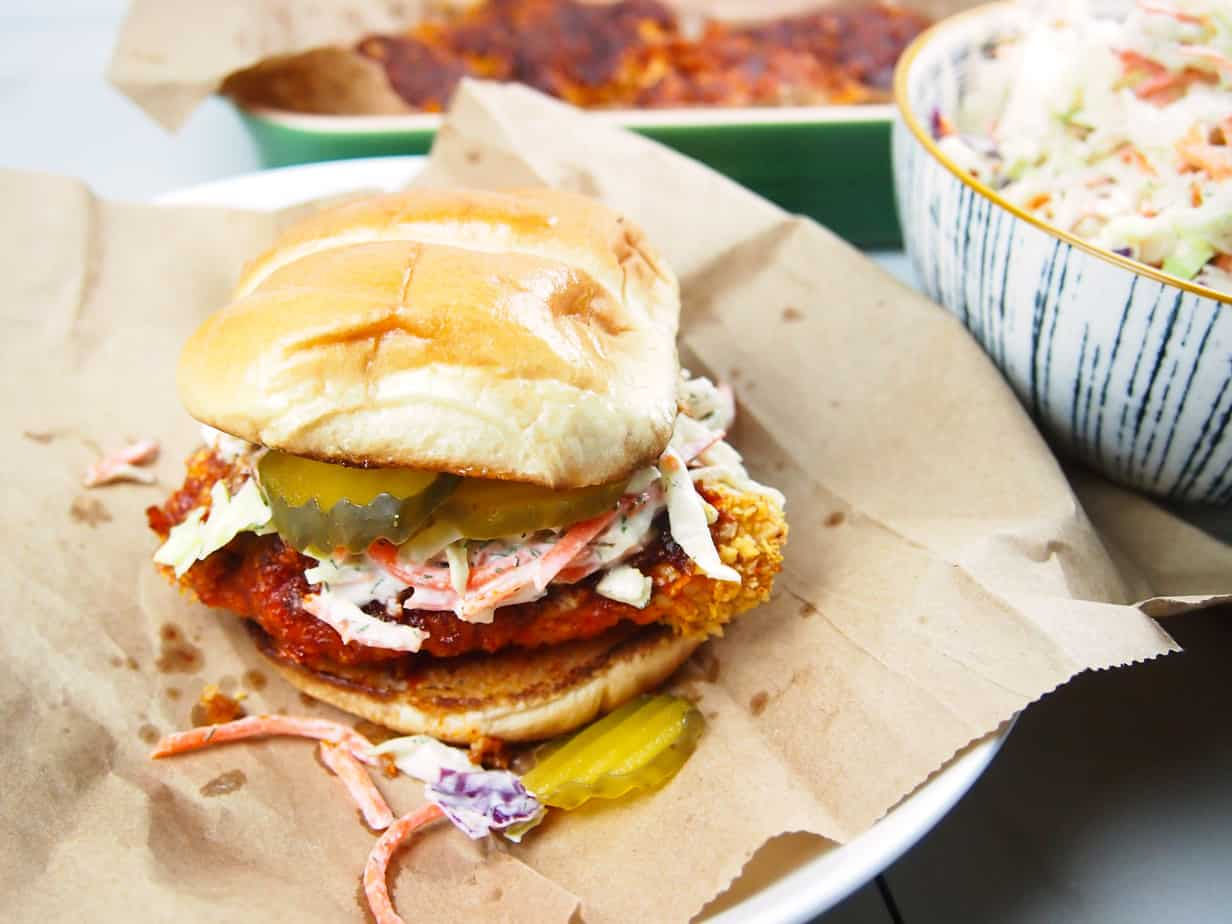 Hot, spicy chicken on a sandwich bun with pickles and dill slaw.