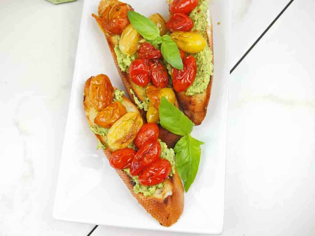 Tomato bruschetta with pesto and basil on a plate