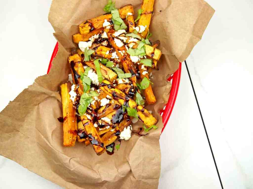 overhead view of loaded Greek fries with feta, basil, and balsamic glaze