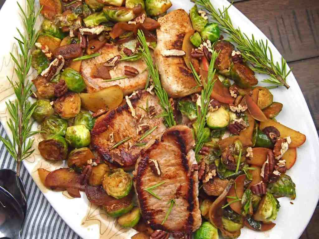 A platter of cider braised pork on a bed of caramelized brussels sprouts