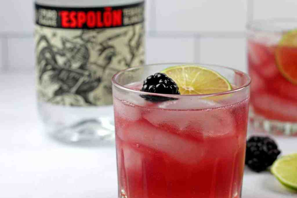 Close up of an el diablo cocktail garnished with a blackberry and lime with a bottle of tequila in the background.