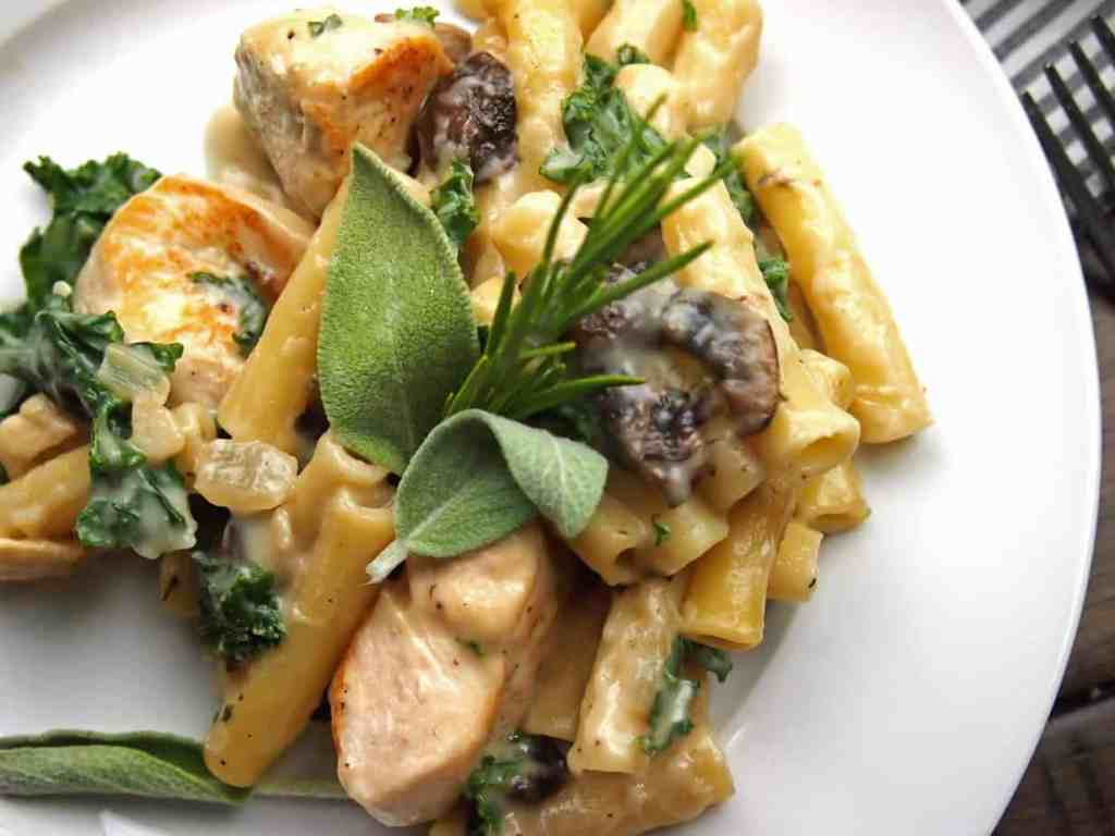 Chicken, mushroom, and kale pasta bake with sage and rosemary on a plate