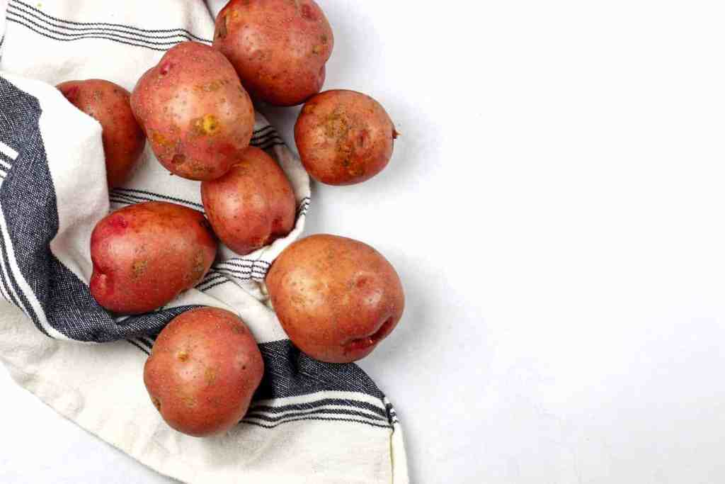 Whole red skin potatoes ready to be made into red skin mashed potatoes on a white surface with a blue and white tea towel
