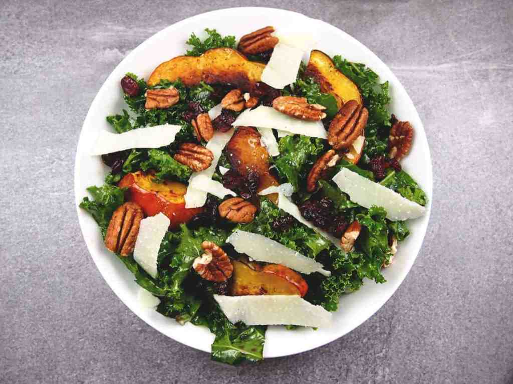 Overview of roasted acorn squash on top of massaged kale salad with pecans, shaved Parmesan, and dried cranberries in a bowl