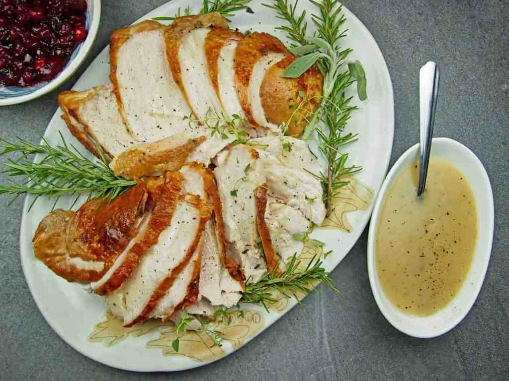 Overview of roasted turkey breast on a platter with gravy and cranberry sauce on the side