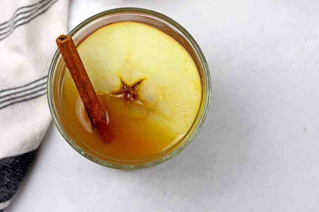 Overview of a apple cider hot toddy with an apple slice and cinnamon stick on a white countertop.