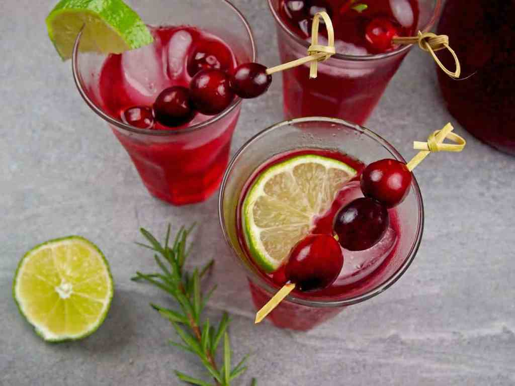 Overview of three glasses of cranberry margaritas with fresh limes, rosemary, and cranberries