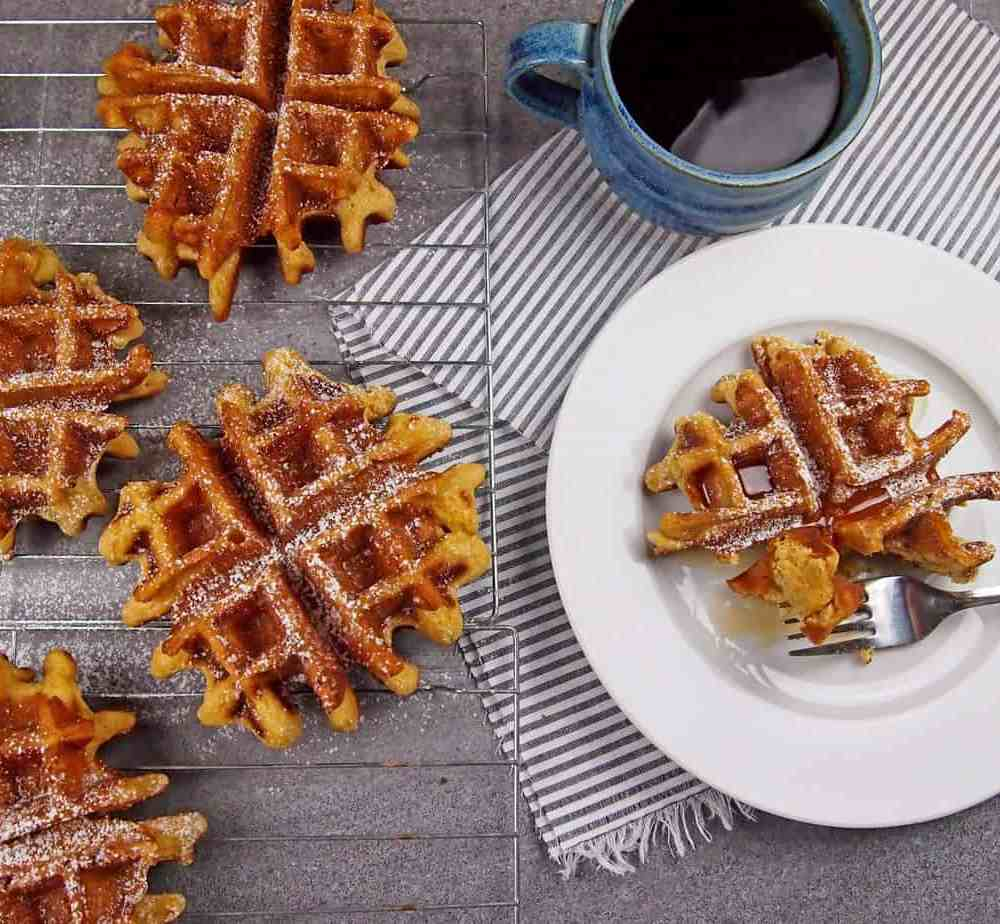 View of eggnog waffles on a cooling rack next to a plate of waffles with syrup and coffee on the side