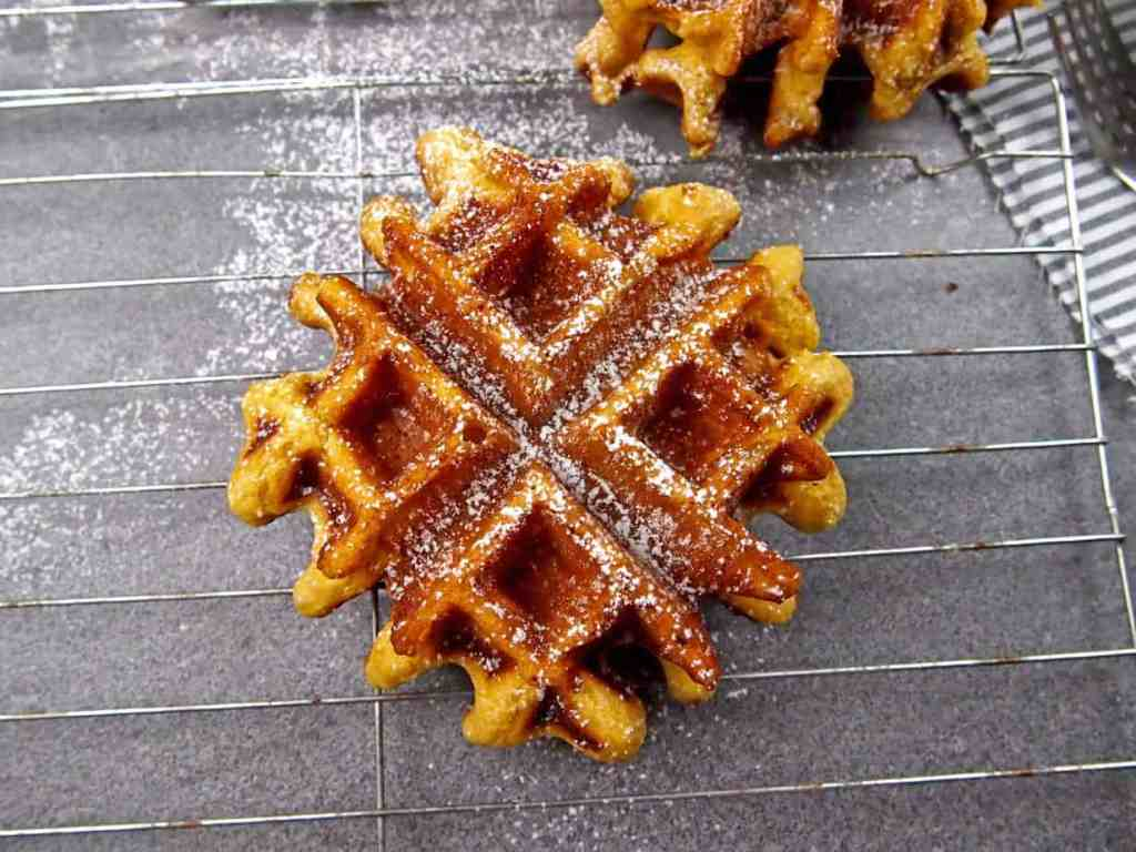 Close up of an eggnog waffle on a cooling rack dusted with powdered sugar