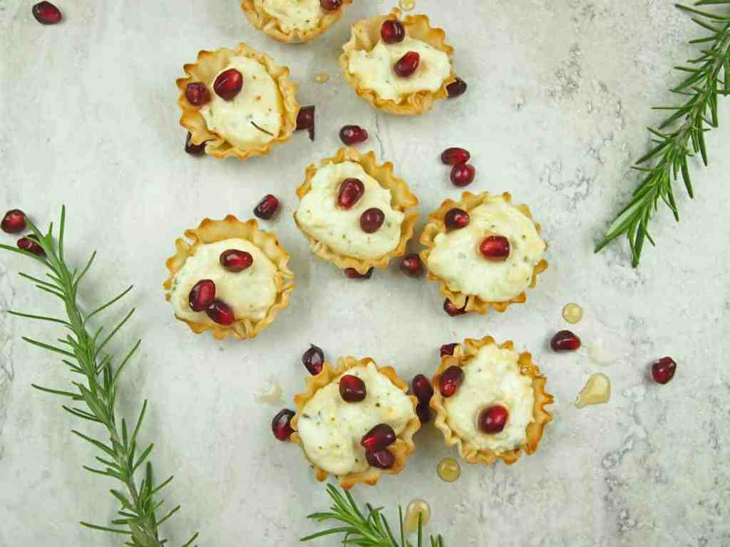 Overview of phyllo cups stuffed with whipped feta with pomegranate seeds and rosemary sprigs