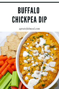 Buffalo chickpea dip surrounded by veggies and crackers on a plate.