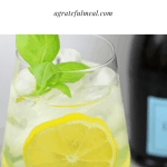 "Limoncello spritz next to a bottle of prosecco with the words ""Lemoncello Spritz agratefulmeal.com"""