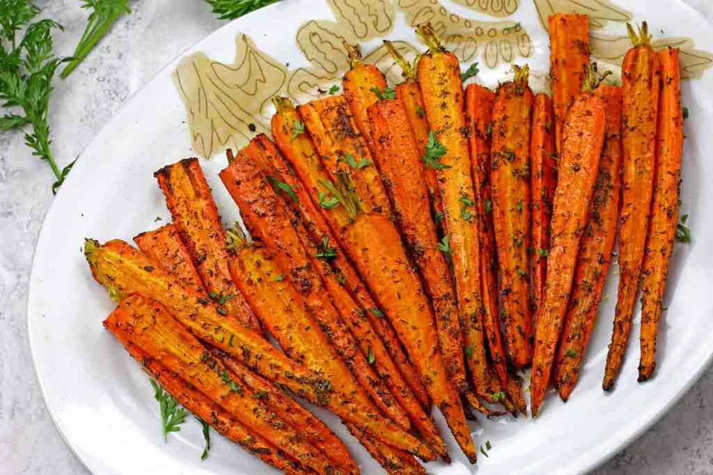 Caramelized air fryer carrots on a plate topped with dill and parmesan