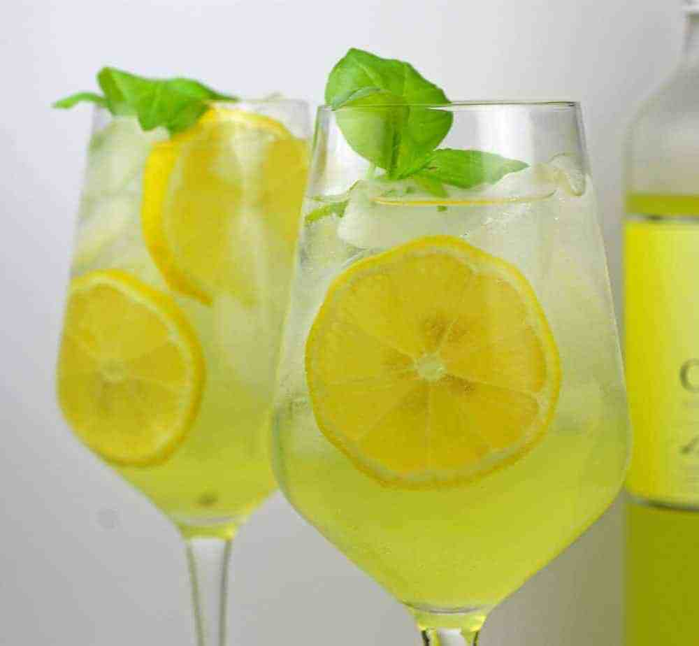 Two glasses of limoncello spritzes with lemon, ice, and basil as garnish with a limoncello bottle in the background.