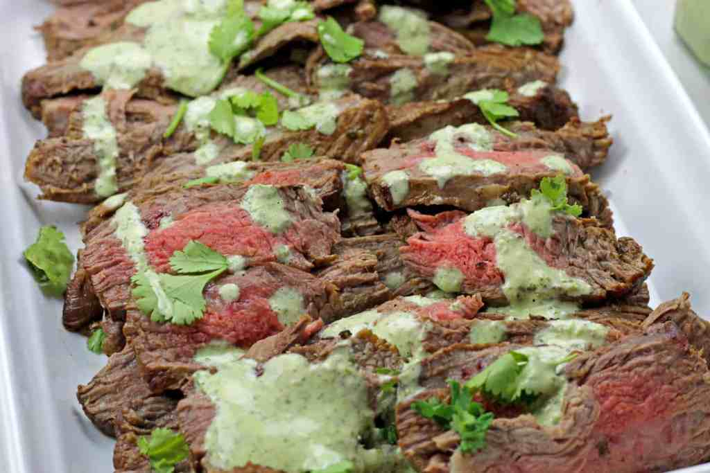 Close of instant pot carne asada on a platter with cilantro garlic sauce drizzled on top.