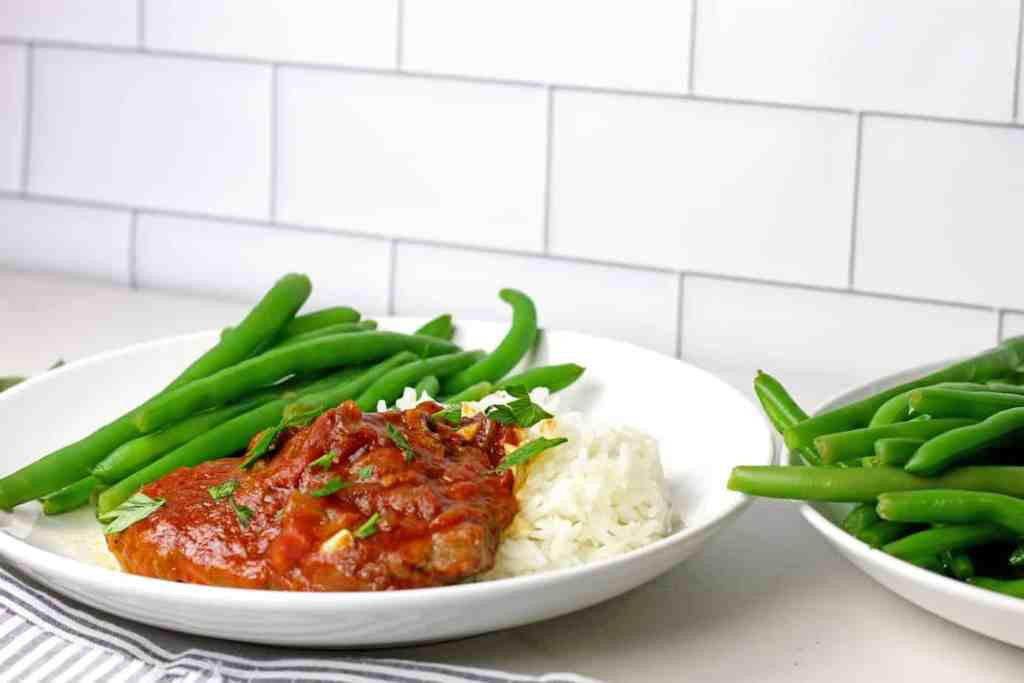 A plate of instant pot swiss steak with green beans and rice on a countertop.