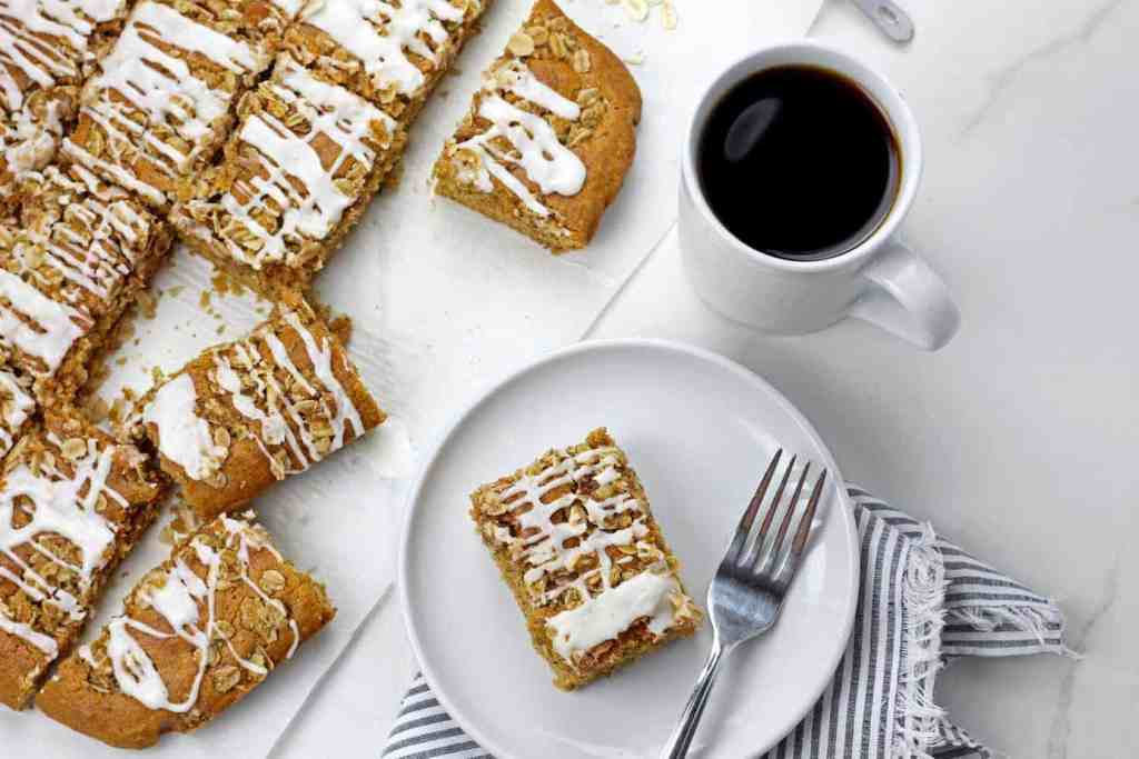 Sliced vegan coffee cake on a white background with a cup of coffee