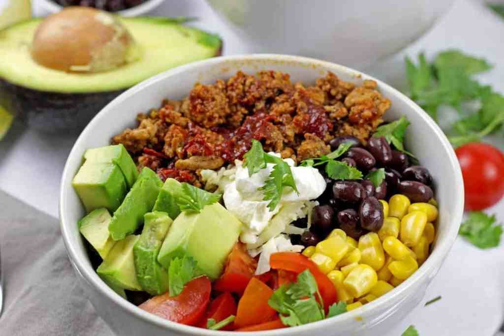 Close up of the turkey taco bowl with avocado, corn, black beans, tomatoes and sour cream