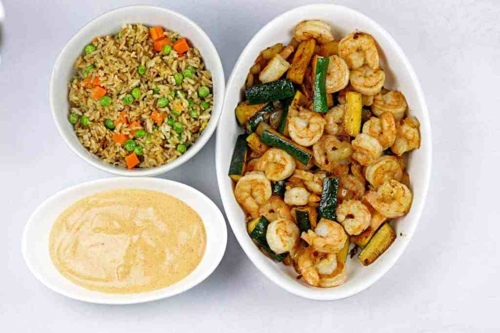 Three white bowls side-by-side filled with fried rice, yum yum sauce, and hibachi shrimp and vegetables