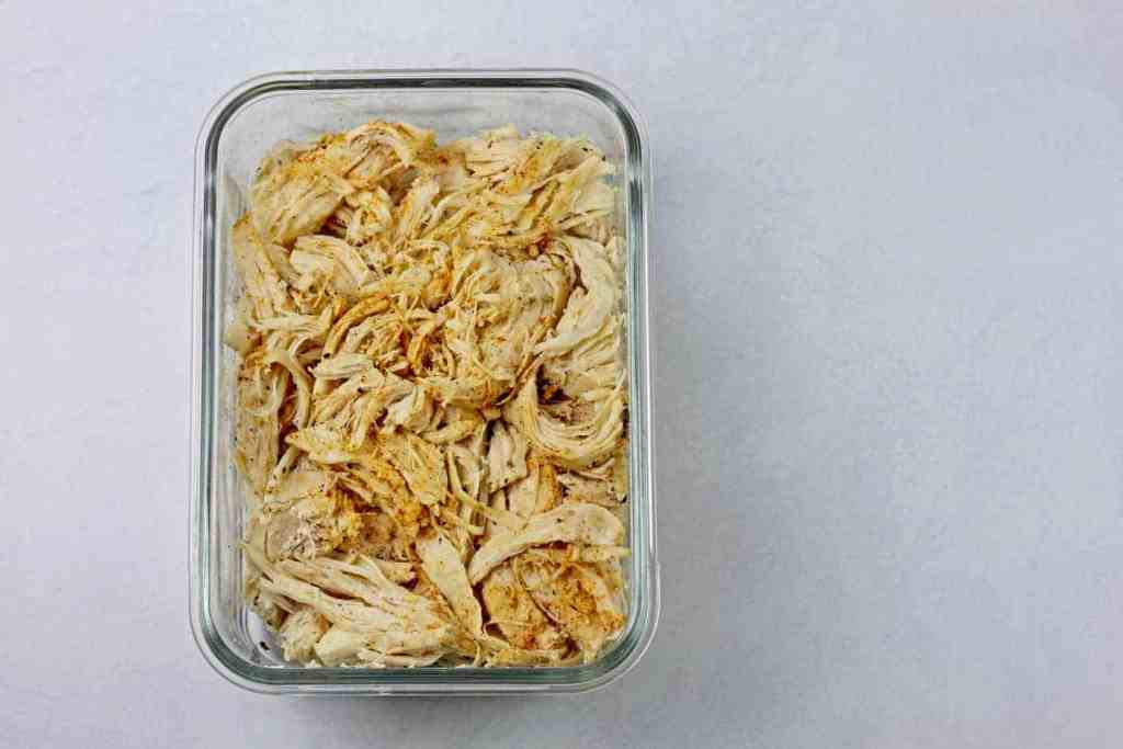 A glass dish filled with instant pot shredded chicken on a white background.