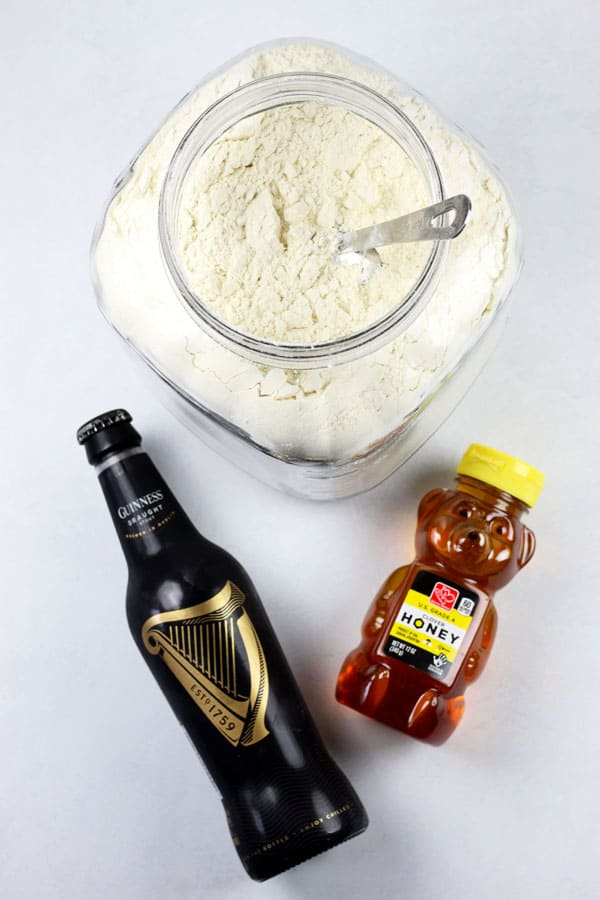 The ingredients for 3 ingredient beer bread on a white background including a bottle of beer, a container of flour with a measuring cup inside, and a bear bottle of honey.