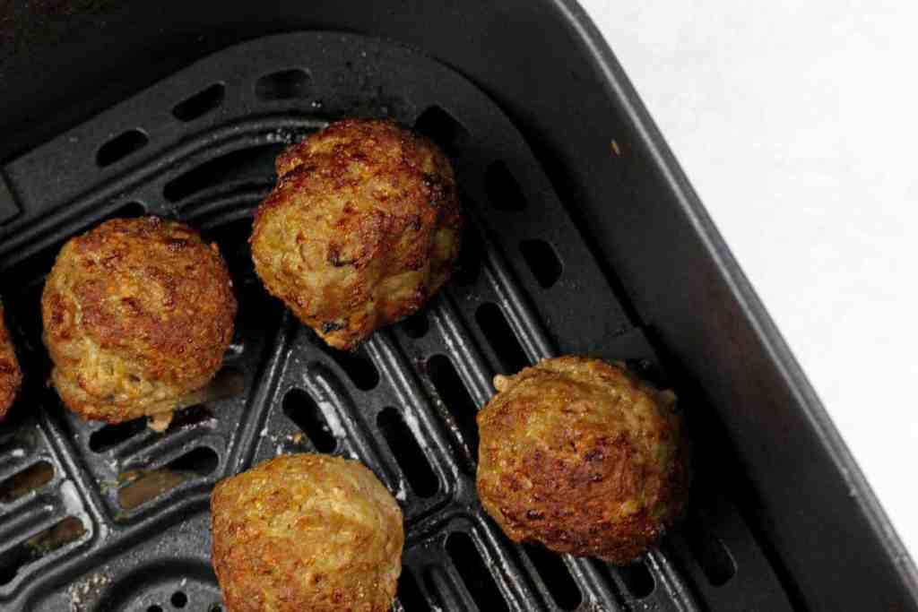 A black air fryer basket with 4 turkey meatballs inside.