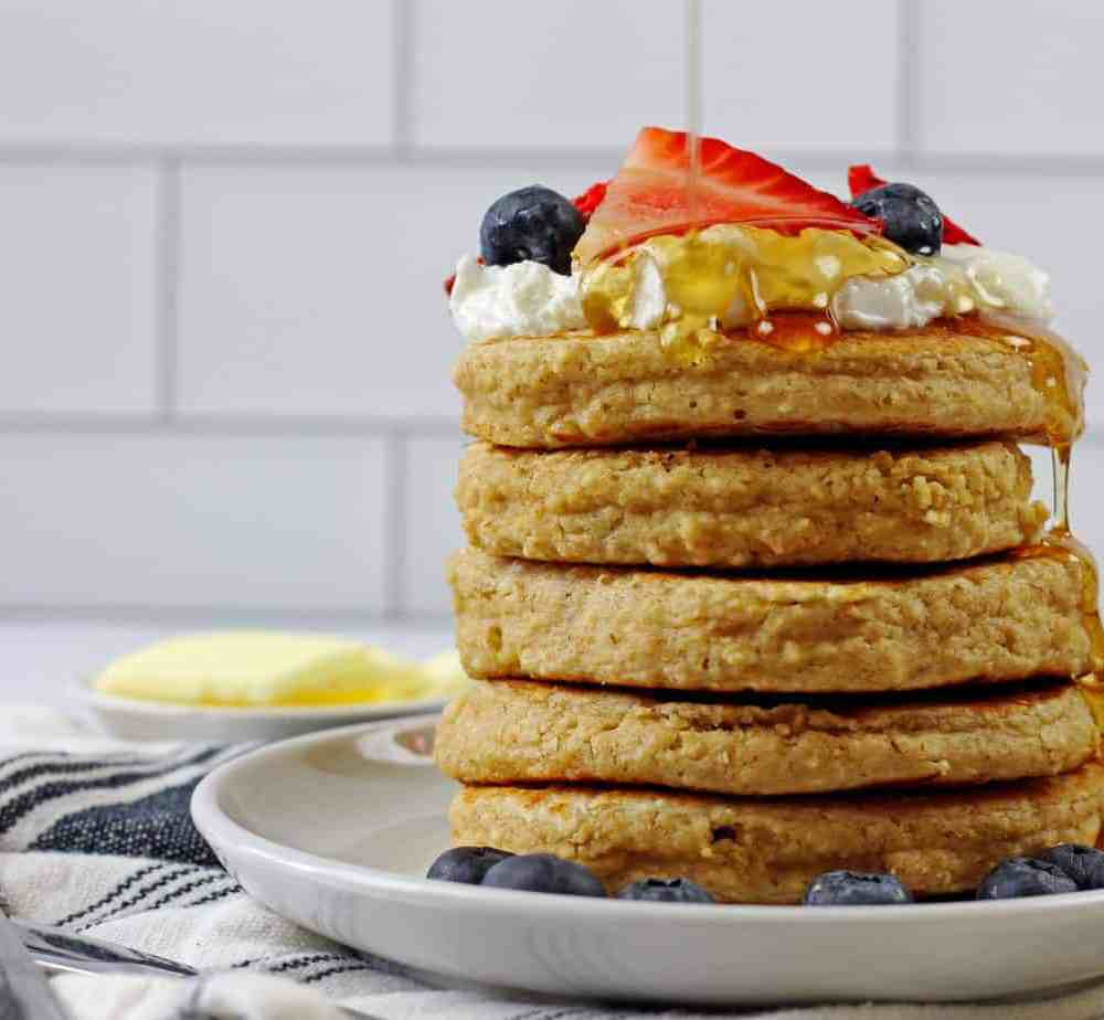 A stack of gluten free oat flour pancakes with yogurt and berries on top. Maple syrup is dripping down the sides of the pancakes. On side there is a napkin and a butter dish with white subway tile in the background.