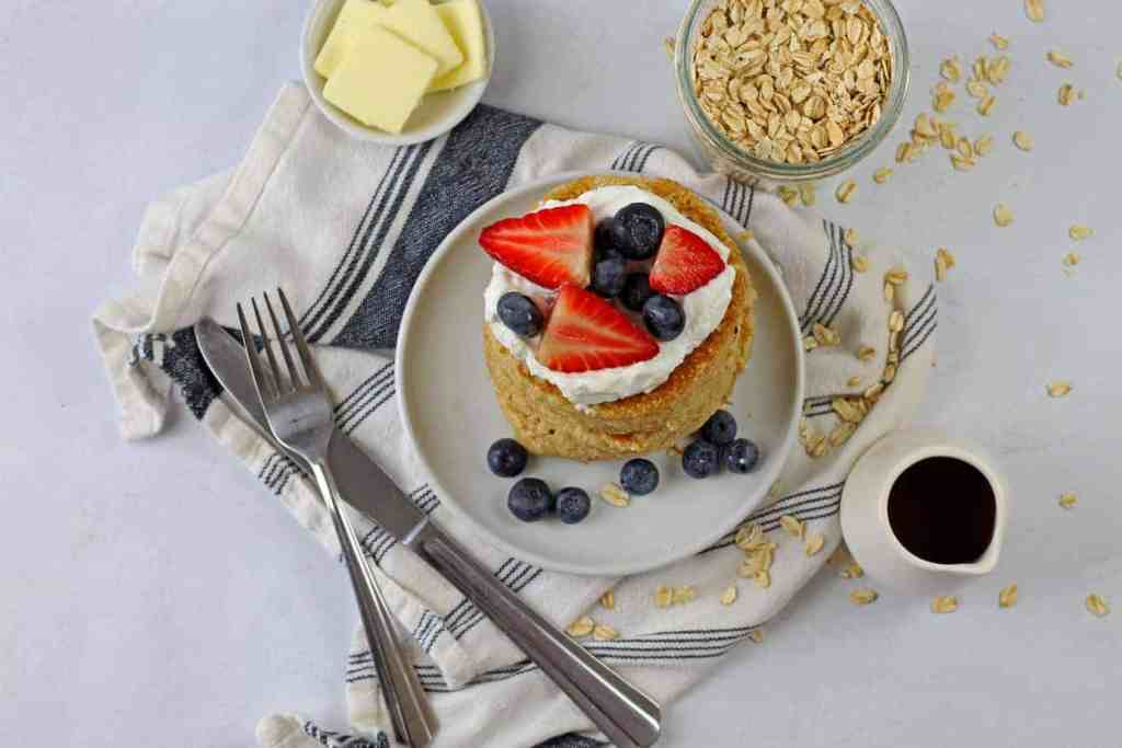 A plate of gluten free oat flour pancakes topped with berries and yogurt with butter, oats, syrup, a blue and white napkin, and silverware on the side on a white background.