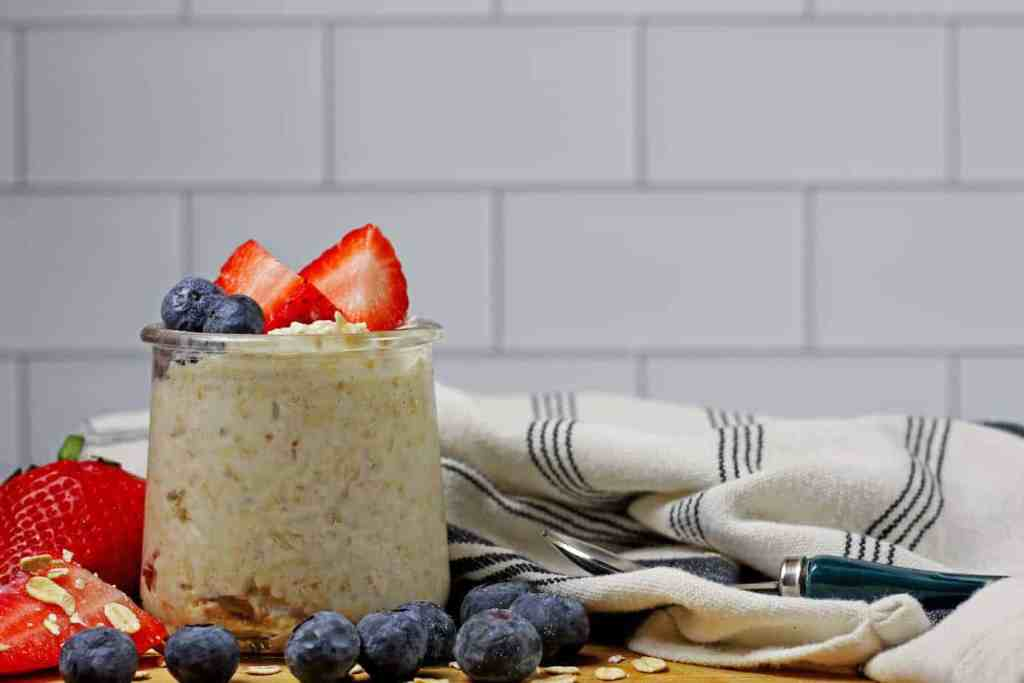 A jar of vanilla overnight oats with berries on a top and on the side on a wooden cutting board and a white and blue napkin on the side. White subway tile is in the background.