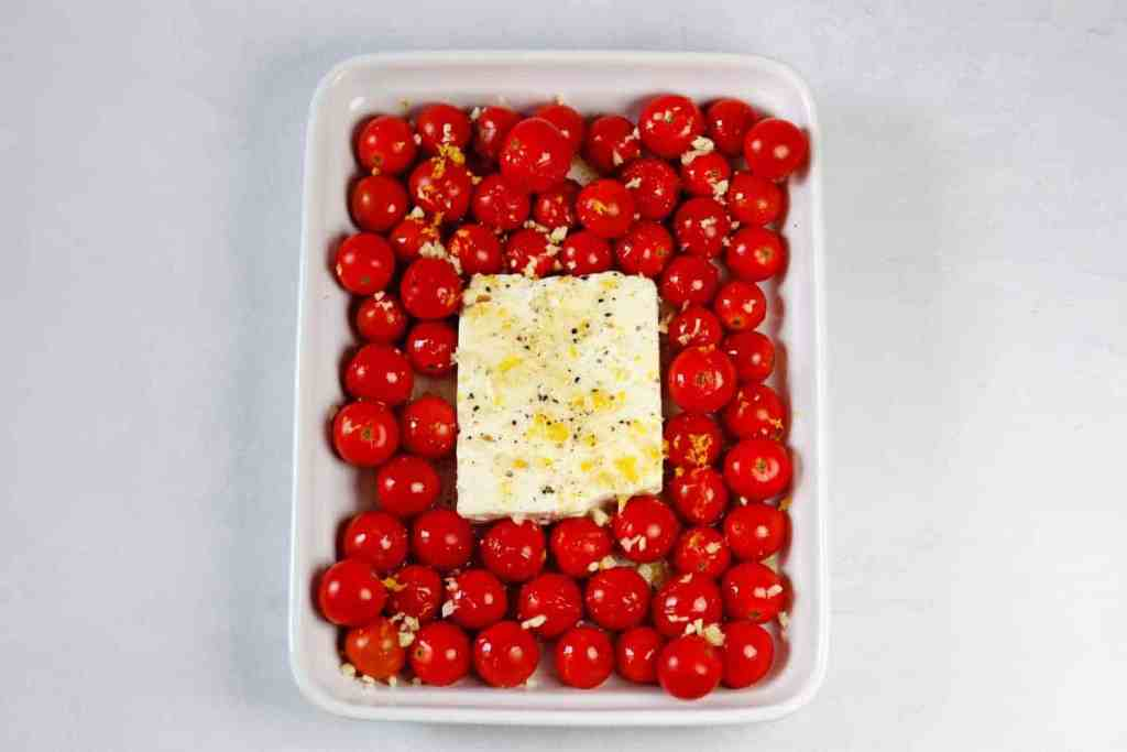 An overhead shot of the feta cheese block in the middle of the cherry tomatoes in a white baking dish on a white countertop. Seasonings and lemon zest are sprinkled on top of the feta cheese.