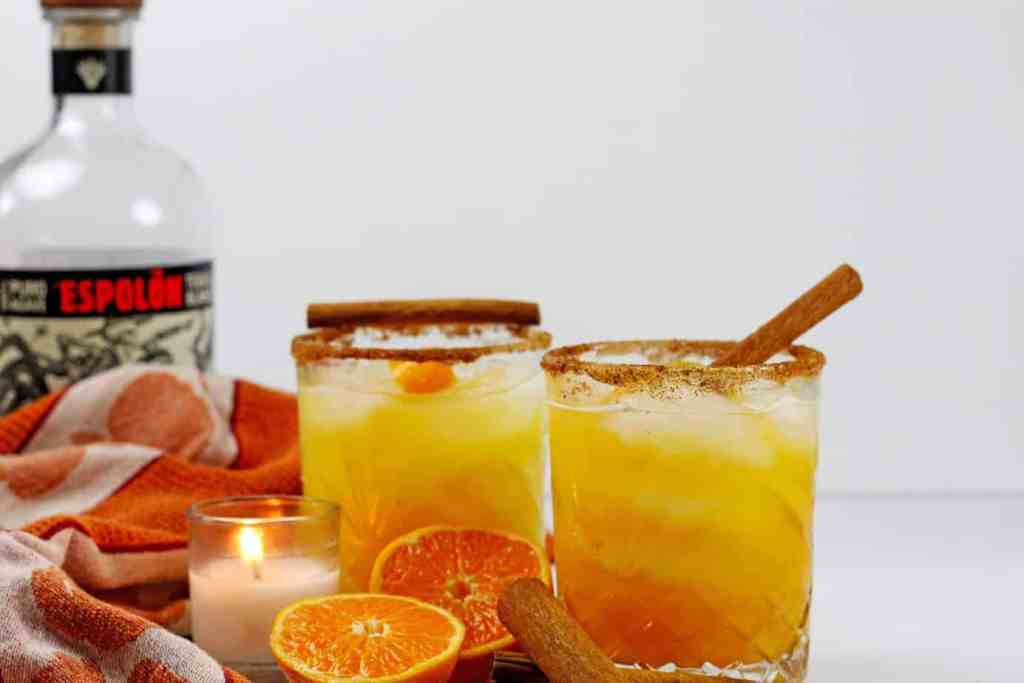 Two glasses of pumpkin spice margaritas with an orange kitchen towel, sliced oranges, a lit candle, and cinnamon sticks next to it. The background is white and there is a tequila bottle in the light gray background.