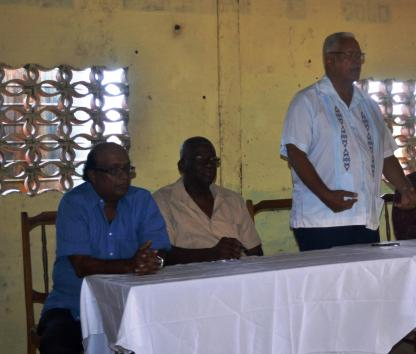 minister-holder-standing-while-addressing-the-gathering-also-at-the-table-ceo-of-narei-dr-oudhoo-homenauth-and-ceo-of-glda-mr-nigel-cumberbatch